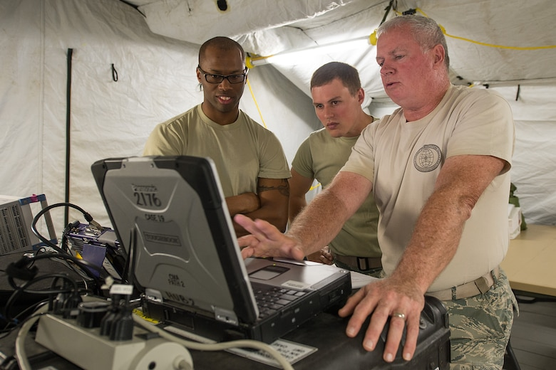An RF transmission superintendent, right, with the 283rd Combat Communications Squadron (CCS) from Dobbins Air Reserve Base, Georgia Air National Guard, discusses satellite transmission data information obtained from a Theater Deployable Communications System with two Airmen from the 117th Air Control Squadron during the Sentry Savannah 15-2 exercise at The Air Dominance Center, Savannah, Ga., May 10, 2015. Sentry Savannah is a National Guard Bureau sponsored training event with a focus on Joint Dissimilar Air Combat Training and 5th Generation Fighter Integration. It offers a chance for fighter pilots to participate in war simulations that depict what they would face in real-world scenarios. During the exercise the 283rd CBCS provided NIPR, SIPR, and voice services to the 117th Air Control Squadron Air Battle Element and extended service to their deployed radar site. Working together the two units provided vital data to help the fighter pilots complete their missions. (U.S. Air National Guard photo by the 116th Air Control Wing Public Affairs/Released) (Names of military personnel have been withheld for security purposes)