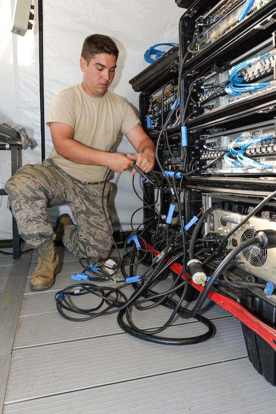A U.S. Air Force cyber systems operator with the 283rd Combat Communications Squadron (CCS) from Dobbins Air Reserve Base, Georgia Air National Guard, connects cables during set up of a Theater Deployable Communications System during the Sentry Savannah 15-2 exercise at The Air Dominance Center, Savannah, Ga., May 8, 2015. Sentry Savannah is a National Guard Bureau sponsored training event with a focus on Joint Dissimilar Air Combat Training and 5th Generation Fighter Integration. It offers a chance for fighter pilots to participate in war simulations that depict what they would face in real-world scenarios. During the exercise the 283rd CBCS provided NIPR, SIPR, and voice services to the 117th Air Control Squadron Air Battle Element and extended service to their deployed radar site. Working together the two units provided vital data to help the fighter pilots complete their missions. (U.S. Air National Guard photo by the 116th Air Control Wing Public Affairs/Released) (Name of military member withheld for security purposes)
