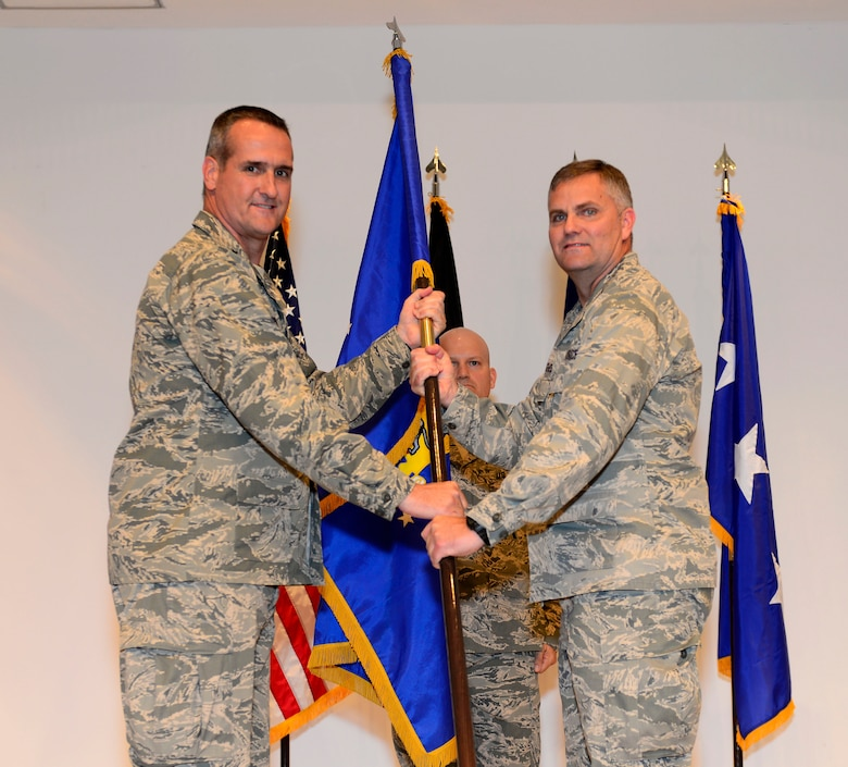U.S. Maj. Gen. Peter Gersten,  Commander of the Ninth Air and Space Expeditionary Task Force, passes the guidon to Col. Michael Koscheski, the 332nd Air Expeditionary Wing commander, during an activation and assumption of command ceremony at an undisclosed location in Southwest Asia May 19, 2015. The 332nd AEW activated as the only combat wing within the Ninth AETF-L. (U.S. Air Force photo by Senior Airman Racheal E. Watson)