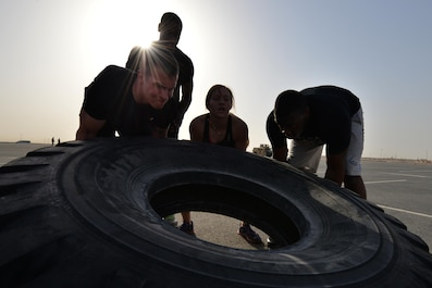 Airmen from the 379th Expeditionary Security Forces Squadron flip a truck tire for a combat challenge as part of National Police week event May 14, 2015 at Al Udeid Air Base, Qatar. National Police was established to honor American law enforcement in 1962 to help gain recognition to officers that have lost their lives in the line of duty. (U.S. Air Force photo by Staff Sgt. Alexandre Montes)