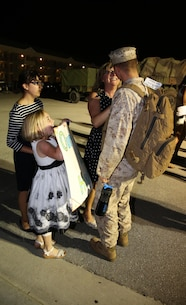 Cpl. Harry M. Aguirre, training clerk with Headquarters and Support Company, Ground Combat Element Integrated Task Force,  wife and daughters welcome him back to Marine Corps Base Camp Lejeune, North Carolina, May 20, 2015, after returning from a three-month assessment at Marine Corps Air Ground Combat Center Twentynine Palms and Marine Corps Mountain Warfare Training Center Bridgeport, California. From October 2014 to July 2015, the GCEITF conducted individual and collective level skills training in designated ground combat arms occupational specialties in order to facilitate the standards-based assessment of the physical performance of Marines in a simulated operating environment performing specific ground combat arms tasks. (U.S. Marine Corps photo by Sgt. Alicia R. Leaders/Released)
