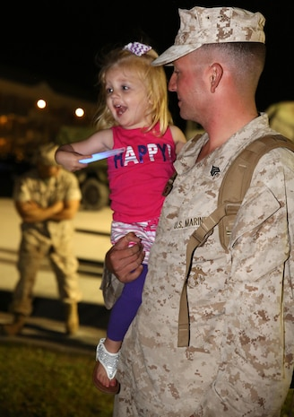 Sgt. Travis J. Smith, combat engineer with Engineer Platoon, Headquarters and Support Company, Ground Combat Element Integrated Task Force, embraces his daughter after returning to Marine Corps Base Camp Lejeune, North Carolina, May 20, 2015, from a three-month assessment at Marine Corps Air Ground Combat Center Twentynine Palms and Marine Corps Mountain Warfare Training Center Bridgeport, California. From October 2014 to July 2015, the GCEITF conducted individual and collective level skills training in designated ground combat arms occupational specialties in order to facilitate the standards-based assessment of the physical performance of Marines in a simulated operating environment performing specific ground combat arms tasks. (U.S. Marine Corps photo by Sgt. Alicia R. Leaders/Released)