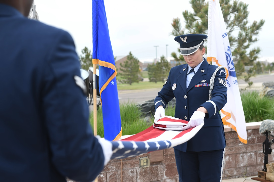 The Mile High Honor Guard retreat the colors during Buckley Air Force Base's Memorial Day ceremony May 21, 2015, at the headquarters building on Buckley AFB, Colo. The ceremony included a formation, a guest speaker who spoke on his experiences during the Vietnam War, and a retreat ceremony. (U.S. Air Force photo by Airman 1st Class Samantha Meadors/Released)