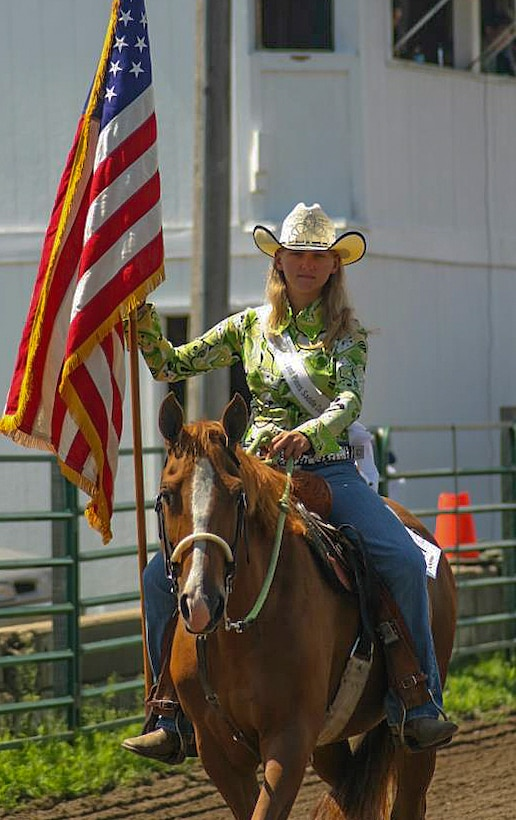 "Alexis Visser, Pequot Lakes, Minn., resident and avid horse rider, carries the flag during the playing of the ""Star Spangled Banner"" at the Crow Wing County Fair in 2013. Visser currently works in the 90th Munitions Squadron on F.E. Warren Air Force Base, Wyo. (Courtesy photo)"
