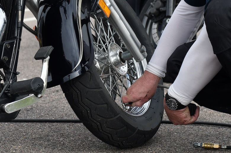 """Rodger Scott, 460th Space Communications Squadron deputy, puts air into the tires of a Team Buckley member's motorcycle before their safety ride May 15, 2015, on Buckley Air Force Base, Colo. The 460th SCS had this motorcycle ride to give """"on-the-job"""" training to ensure young members of the squadron know how to ride safely. (U.S. Air Force photo by Airman 1st Class Emily E. Amyotte/Released)"""