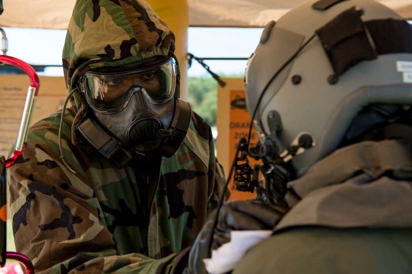 U.S. Air Force Airman 1st Class Michael Gibbs-Forde, an aircrew flight equipment journeyman with the 437th Operations Support Squadron, assists Airman 1st Class Matthew Link, a C-17 loadmaster with the 16th Airlift Squadron, at a Crescent Reach 15 decontamination station May 20, 2015, at Joint Base Charleston, S.C. This local exercise, which tested and evaluated Joint Base Charleston's ability to launch a large aircraft formation in addition to process and deploy duty passengers and cargo in response to a simulated crisis abroad from May 18-21. Deploying members' ability to survive and operate in deployed environments was also exercise through Chemical, Biological, Radiological, Nuclear Explosives training and evaluation events. (U.S. Air Force photo by Staff Sgt. Jamal D. Sutter)
