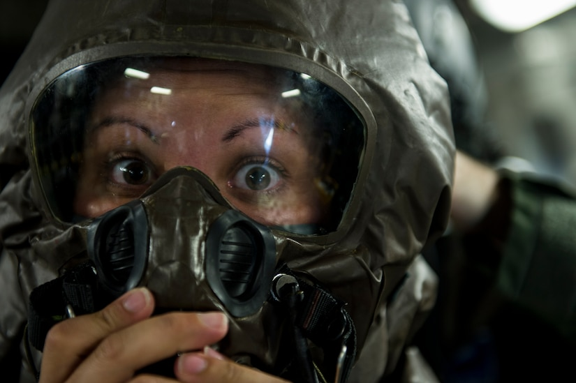 U.S. Air Force Senior Airman Amanda Fields, a C-17 loadmaster with the 17th Airlift Squadron, widens her eyes for the camera as a co-worker secures her mission-oriented protective posture gear May 20, 2015, during Crescent Reach 15 at Joint Base Charleston, S.C. This local exercise, which tested and evaluated Joint Base Charleston's ability to launch a large aircraft formation in addition to process and deploy duty passengers and cargo in response to a simulated crisis abroad from May 18-21. Deploying members' ability to survive and operate in deployed environments was also exercise through Chemical, Biological, Radiological, Nuclear Explosives training and evaluation events. (U.S. Air Force photo by Staff Sgt. Jamal D. Sutter)