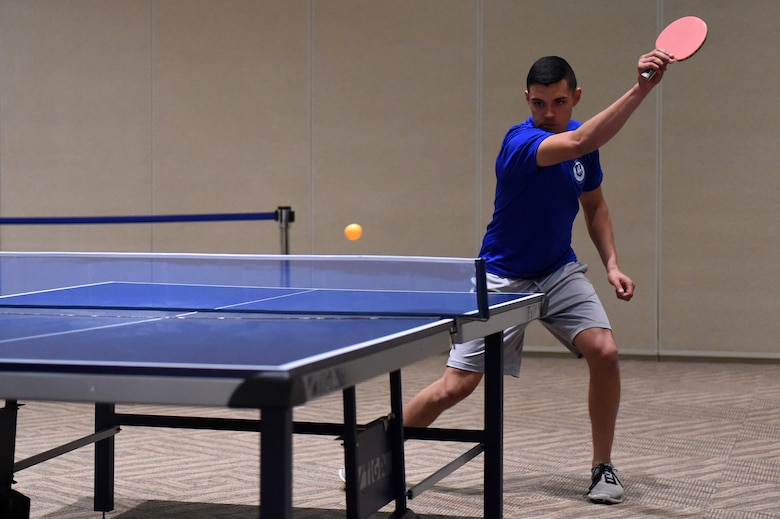 A table tennis player hits the ball during the Tri-Wing Sports Day competition May 20, 2015, on Buckley Air Force Base, Colo. Tri-Wing Sports Day is held once a year between the three Air Force Space Command bases and is intended to promote healthy, active lifestyles and friendly competition. The bases competed against each other in over 15 sports such as volleyball, football, tennis and softball among others. (U.S. Air Force photo by Airman 1st Class Emily E. Amyotte/Released)
