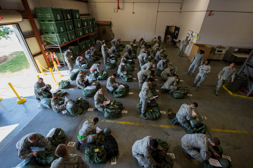 U.S. Air Force Airmen perform mobility bag inventory during Crescent Reach 15 May 2015. This local exercise tested and evaluated Joint Base Charleston's ability to launch a large aircraft formation in addition to process and deploy duty passengers and cargo in response to a simulated crisis abroad May 18-21. Deploying members' ability to survive and operate in deployed environments was also exercised through Chemical, Biological, Radiological, Nuclear Explosives training and evaluation events. (U.S. Air Force photo by Staff Sgt. Jamal D. Sutter)