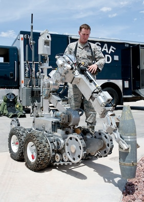 Senior Airman Wyland Wacaser, 99th Civil Engineer Squadron explosive ordnance disposal journeyman, operates the F6A robot by picking up an inert unexploded ordnance on Nellis Air Force Base, Nev., May 13, 2015. Airmen at EOD can work alongside the Las Vegas Metropolitan Police and  Fire Departments if there is any military ordnance or if advice is wanted. (U.S. Air Force photo by Airman 1st Class Jake Carter)