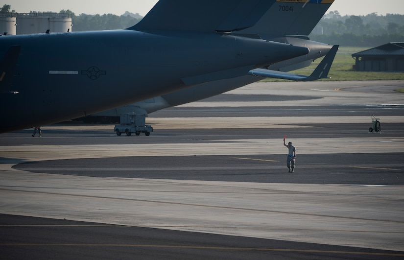 An Airman clears the side of a C-17 May 21, 2015, at Joint Base Charleston, S.C. during exercise Crescent Reach 2015. The exercise tested JB Charleston's ability to launch a large aircraft formation and mobilize a large amount of cargo and passengers. (U.S. Air Force photo/Senior Airman Jared Trimarchi)