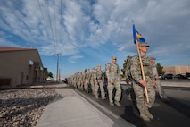 Airmen assigned to the 99th Security Forces Squadron march down the road halfway through the National Police Week 10K memorial ruck march at Nellis Air Force Base, Nev., May 13, 2015. Throughout the march, the formation stopped at various hydration stations and rendered honors to fallen security forces Airmen. (U.S. Air Force photo by Senior Airman Joshua Kleinholz)