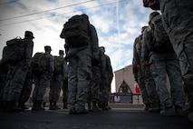 Lt. Col. Joseph Ringer, 99th Security Forces Squadron commander, leads his formation in recognition of Airman First Class Elizabeth Jacobson during the National Police Week 10K memorial ruck march at Nellis Air Force Base, Nev., May 13, 2015. Jacobson, a security forces Airman who was killed performing convoy security in support of Operation Iraqi Freedom, was honored along with other fallen members of the law enforcement community at the numerous stops made by the formation along their route. (U.S. Air Force photo by Senior Airman Joshua Kleinholz)