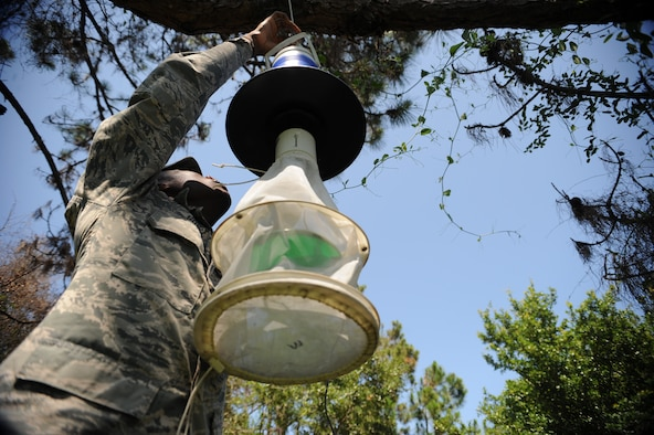 Airman 1st Class Alexander Govan Jr., 6th Aerospace Medicine Squadron public health technician, sets up a mosquito trap at MacDill Air Force Base, Fla., May 20, 2015. After 24- hours, Govan collects the mosquitoes to be frozen in the lab before separating the females and sending them to Wright-Patterson AFB to be tested for diseases, such as malaria, by the head entomologist. (U.S. Air Force photo by Airman 1st Class Danielle Conde/Released)