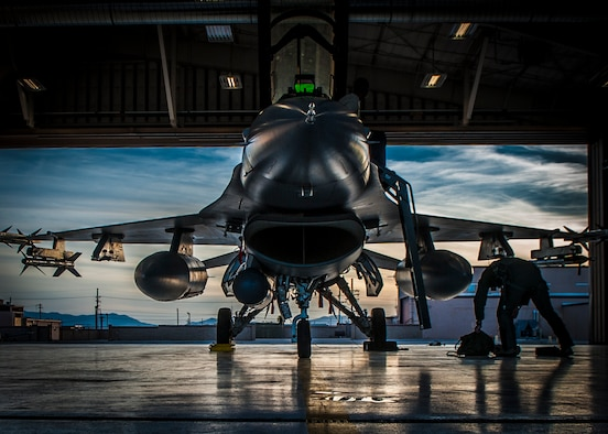 An F-16 Fighting Falcon sits in a hangar prior to departure at Holloman Air Force Base, N.M. May 13, 2015. F-16 students from the 311th Fighter Squadron, a tenant until from Luke Air Force Base, Ariz., are currently flying night operations as part of their syllabus. During the night operations, the students are becoming familiarized with night vision goggles while performing combat training missions. (U.S. Air Force photo by Airman 1st Class Emily A. Kenney/Released)
