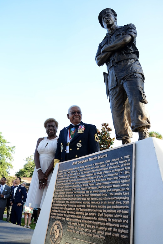 U.S. Army Sgt. 1st Class Melvin Morris, Medal of Honor recipient, his wife, Mary, stand next to a live-size bronze statue of himself; standing arms crossed, in his 1960's era Army fatigues during a ceremony, which included an unveiling, May 14, 2015, at Riverfront Park in Cocoa, Fla. The President, in the name of Congress, has awarded more than 3,400 Medals of Honor to our nation's bravest Soldiers, Sailors, Airmen, Marines, and Coast Guardsmen since the decoration's creation in 1861. (Photo courtesy/Florida Today)
