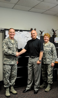 Col. Patrick Rhatigan, 19th Airlift Wing commander, along with Chief Master Sgt. Rhonda Buening, 19th Airlift Wing command chief, congratulate Mike Webster, a 19th Communications Squadron plans and programs project manager, for his selection as Combat Airlifter of the Week May 18, 2015, at Little Rock Air Force Base, Ark. Webster oversaw information technology requirements for 11 major projects on Little Rock Air Force Base, totaling $8.3 million. (U.S. Air Force photo by Senior Airman Stephanie Serrano)