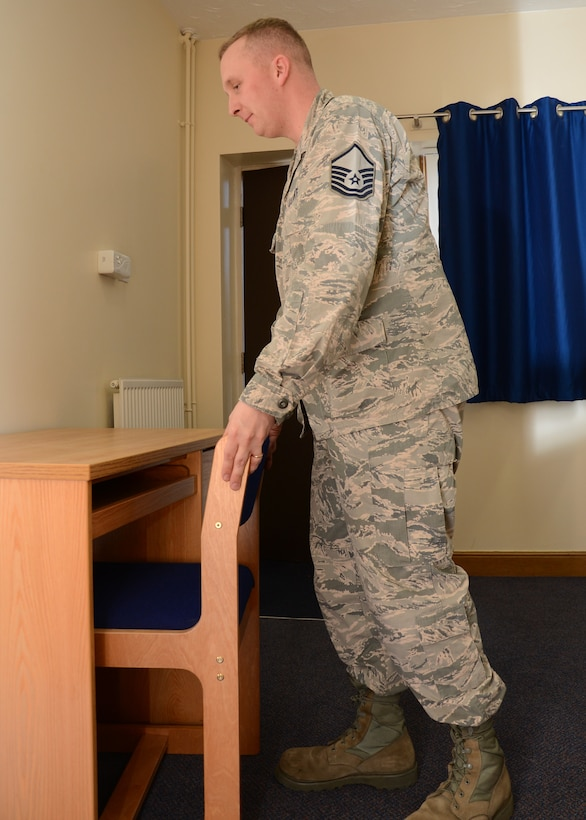 U.S. Air Force Master Sgt. Kenneth Oliver, 100th Civil Engineer Squadron Unaccompanied Housing superintendent from Woolwich, Maine, places a chair in a dormitory March 24, 2015, on RAF Mildenhall, England. The 100th CES recently renovated Dorm 111 and had the kitchen and bathrooms fully refitted, new appliances installed and new bedroom furniture, as well as having the vanity units replaced. (U.S. Air Force photo by Gina Randall/Released)