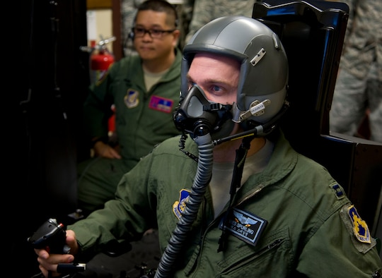 U.S. Air Force Capt. Wes Spurling, 8th Operations Support Squadron operations flight commander assigned to Kunsan Air Base, Republic of Korea, simulates flying in a hypoxia familiarization trainer at Misawa AB, Japan, May 20, 2015. Pilots are required to participate in this training to understand how their bodies react to a deficient amount of oxygen reaching their body, called hypoxia. (U.S. Air Force photo by Airman 1st Class Jordyn Fetter/Released)