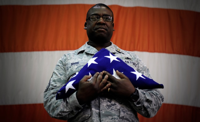 Chief Master Sgt. Lee Barr, 8th Fighter Wing command chief, holds an American flag folded by the 8th FW honor guard as part of his retirement ceremony at Kunsan Air Base, Republic of Korea, May 12, 2015. Barr spent 22 years in the security forces career field while supporting and deploying in Operations Desert Shield and Storm, Southern Watch, Noble Eagle, Iraqi Freedom and Odyssey Dawn. He will have served in the Air Force for 30 years when he retires in November. (U.S. Air Force photo by Senior Airman Taylor Curry/Released)