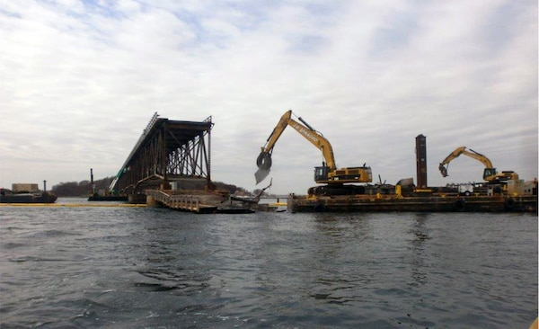 Contractor Walsh Construction removes and sorts bridge debris with barges and excavators during the demolition of the Long Island Bridge in Boston Harbor in Quincy and Boston, Massachusetts on April 6, 2015.