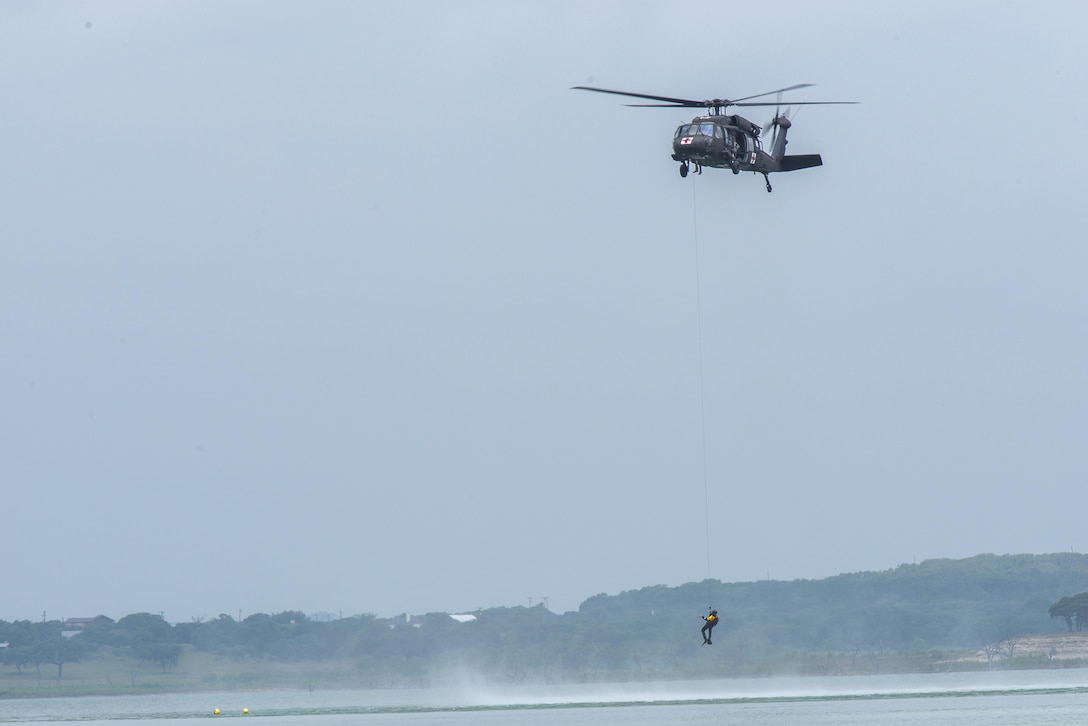 A rescue swimmer is lowered to the water during a helicopter search and rescue training event May 7, 2015, at Canyon Lake, Texas. Members of the Texas Army National Guard's 39th Flying Training Squadron, Task Force 1 and the Texas Parks and Wildlife Department trained together to remain proficient in their water rescue and survival techniques. (U.S. Air Force photo/Airman 1st Class Stormy Archer)