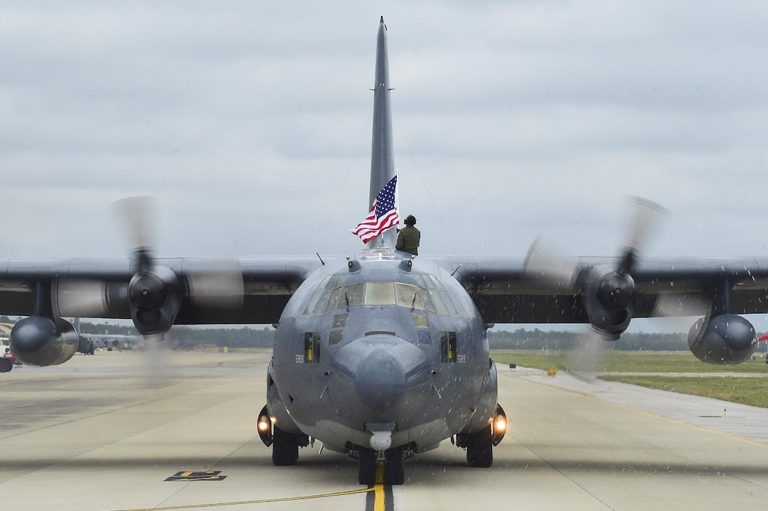 Tech. Sgt. Bruce Ramos, a 1st Special Operations Group Detachment 1 radio operator, raises an American flag from an MC-130P Combat Shadow while it taxis at Hurlburt Field, Fla., May 15, 2015. The final two MC-130Ps in the Air Force landed for the last time at Hurlburt Field in front of more than 400 people, and will take their last flight to the boneyard at Davis-Monthan Air Force Base, Ariz., June 1. (U.S. Air Force photo/Senior Airman Jeff Parkinson)