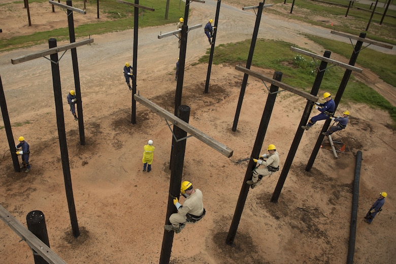 Airmen climb utility poles during the electronic systems apprentice or power line distribution course at Sheppard Air Force Base, Texas, May 19, 2015. The students learn how to use, install and maintain electrical equipment necessary for mission success. (U.S. Air Force photo/Senior Airman Kyle Gese)