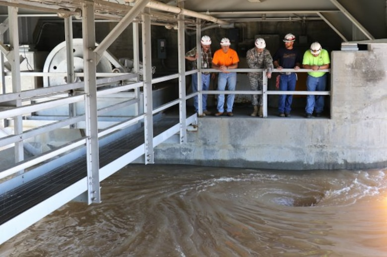 Col. Richard A. Pratt, U.S. Army Corps of Engineers, Tulsa District, commander (center), Mike Abate, with the District's Civil Works Branch (far left) and members of the Eufaula Lake Dam operations and maintenance team, obverse water spiraling down through one of the dam's Tainter gates, as the amount of water being released through the gates was increased from 48,000 to 62,000 cubic feet per second, May 18, 2015.
