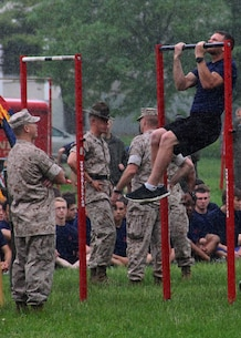 GySgt Gene E. Bradley, SNCOIC of Recruiting Sub Station North Indianapolis, counts a poolee's pull-ups in the rain during Recruiting Station Indianapolis' 2015 Statewide Pool Function in Indianapolis, Indiana May 16, 2015. The young men and woman train to become the next generation of America's tough, smart and elite warriors by preparing their minds and bodies for the rigors of Marine Corps recruit training.