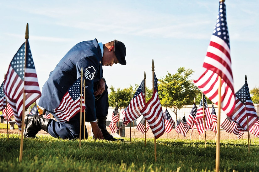 Air Force Master Sgt. Robert Lilly pays his respects to a fallen veteran May 28, 2013, at the Southern Nevada Veterans Memorial Cemetery, Boulder City, Nevada. Lilly and other Airmen from Nellis Air Force Base, Nev., volunteered their time to place flags over veterans' cemetery plots for Memorial Day weekend. Lilly is a 57th Operations Group joint terminal air controller. (U.S. Air Force photo/Senior Airman Daniel Hughes)