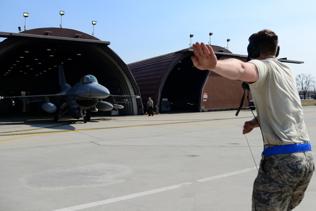 Airman 1st Class Matthew Rzeczycki, 51st Maintenance Squadron crew chief, marshals an F-16 Fighting Falcon during Buddy Wing 15-3 March 26, 2015, at Osan Air Base, Republic of Korea. The purpose of the Buddy Wing program is to exchange ideas, introduce tactics and improve interoperability between the U.S. and Republic of Korea Air Forces. (U.S. Air Force photo by Senior Airman Matthew Lancaster)