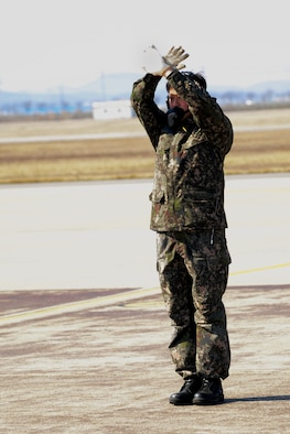 A Republic of Korea air force crew chief marshals an F-16 Fighting Falcon during Buddy Wing 15-3 March 25, 2015, at Osan Air Base, ROK. The program is an opportunity for U.S. Air Force and ROKAF pilots to interact during a smaller scale exercise. (U.S. Air Force photo by Senior Airman Matthew Lancaster)