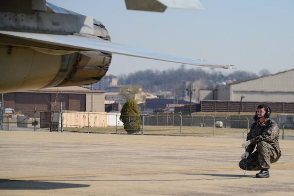 A Republic of Korea air force crew chief  performs pre-flight checks during Buddy Wing 15-3 March 25, 2015, at Osan Air Base, ROK. During Buddy Wing, members from each air force share tactics and procedures to become familiar with how each other work during flying missions. (U.S. Air Force photo by Senior Airman Matthew Lancaster)