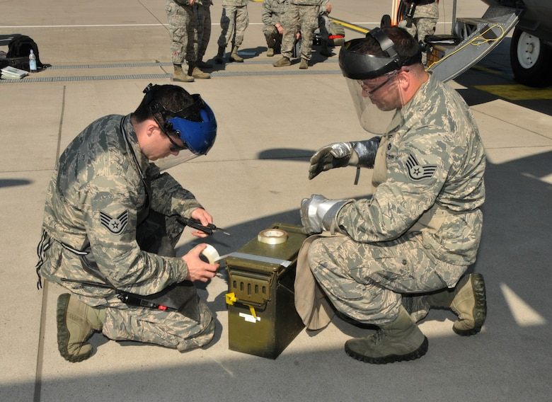 "The non-commissioned officer in charge of equipment, and the non-commissioned officer in charge of operations, 104th Explosive Ordnance Flight (EOD), 104th Fighter Wing, Barnes Air National Guard Base, Westfield, Mass., cut duct tape to secure flares to safe the C-130 aircraft, May 13, 2015, Ramstein, Air Base Germany. The Airmen are emergency responders who will be qualified on ""Safeing"" the C-130 aircraft, making him more valuable to the 104th Fighter Wing and New England area. (U.S. Air National Guard photo by Tech. Sgt. Melanie J. Casineau/Released)"