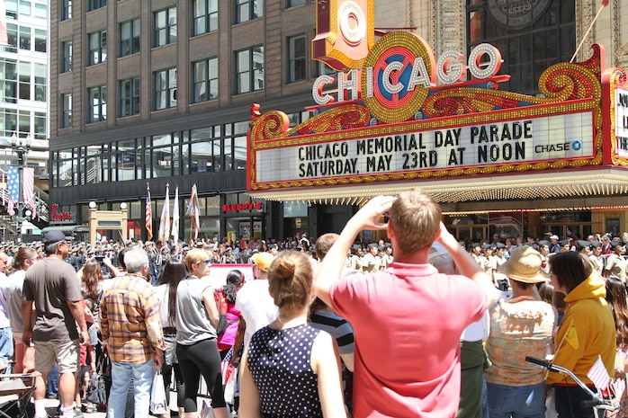 Spectators at the 2015 Chicago Memorial Day parade take photos as one of the many floats, marching bands and JROTC units pass by the Chicago Theater May 23, 2015. The annual parade is considered one of the largest in the nation and attracts thousands of visitors each year to remember those who have paid the ultimate sacrifice for American freedom.