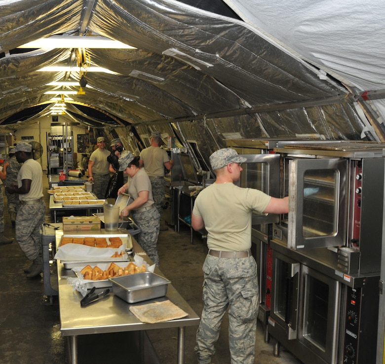 Members from the 104th Services Flight, Barnes Air National Guard Base, Westfield, Mass., prepare dinner in a busy kitchen May 13, 2015, during Exercise Silver Flag, Ramstein Air Base, Germany. Silver Flag is a U.S. Air Force training course designed to educate airman with valuable skills allowing them to know how to deploy using real-world equipment in real-world scenarios. (U.S. Air National Guard photo by Tech. Sgt. Melanie J. Casineau/Released)