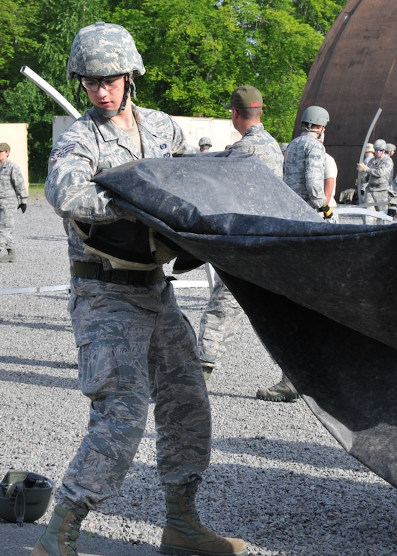 An Airman from the 104th Emergency Management Flight, Barnes Air National Guard Base, Westfield, Mass., carries a fly cover for a Triple-S tent, May 12, 2015, Ramstein Air Base, Germany. He is building a tent with other active duty, guard and reserve members in preparation for Exercise Silver Flag. (U.S. Air National Guard photo by Tech. Sgt. Melanie J. Casineau/Released)