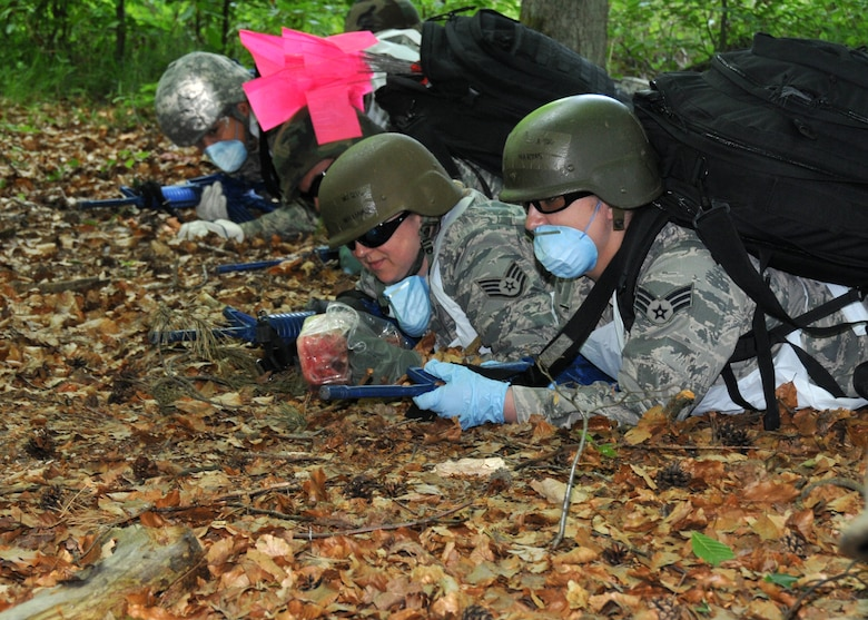 Airmen from the 104th Services Flight, Barnes Air National Guard Base, Westfield, Mass., take cover from simulated enemy fire during an expedited search and recovery exercise May 13, 2015, during Exercise Silver Flag. Silver Flag is an eight-day training exercise designed to prepare Airmen for bare-base deployments. (U.S. Air National Guard photo by 2nd Lt. Bonnie Harper/Released)