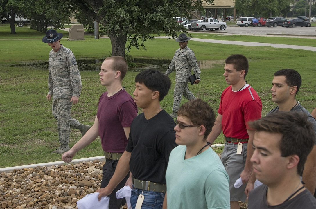 Master Sgt. Joseph Dole (left) and Tech. Sgt. Edroy Robinson, both 331st Training Squadron military training instructors, march newly arrived Air Force basic trainees while marching May 20, 2015, at Joint Base San Antonio-Lackland, Texas. Military training instructors are vital to maintaining the world's greatest Air Force. In 7 ½ weeks, MTIs transform America's sons and daughters from civilians into Airmen by instilling discipline, attention to detail, esprit de corps and challenging them physically and mentally. (U.S. Air Force photo by Johnny Saldivar)