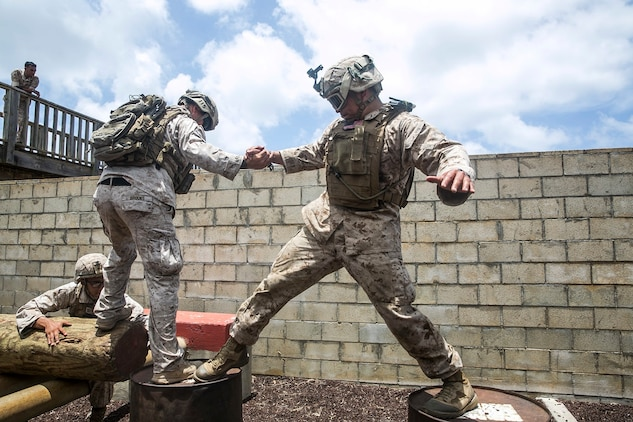 U.S. Marines with the 15th Marine Expeditionary Unit's Maritime Raid Force work together to complete an obstacle at a leadership reaction course aboard Marine Corps Base Hawaii, May 18, 2015. All of the obstacles required a great amount of teamwork and initiative, building the Marines leadership skills and confidence in each other's leadership abilities. (U.S. Marine Corps photo by Cpl. Anna Albrecht/Released)