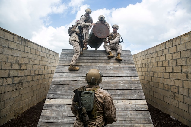 U.S. Marines with the 15th Marine Expeditionary Unit's Maritime Raid Force participate in a leadership reaction course aboard Marine Corps Base Hawaii, May 18, 2015. In this obstacle, the Marines had to get all personnel, gear, equipment, and the barrel over the bridge without letting the barrel touch the wood. This course is designed to make sure everyone can work as a leader and work with a team. (U.S. Marine Corps photo by Cpl. Anna Albrecht/Released)