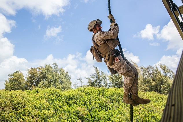 U.S. Marine Lance Cpl. Jose Cortez fast ropes from a tower aboard Marine Corps Base Hawaii, May 12, 2015. Cortez is part of the security element with the 15th Marine Expeditionary Unit's Maritime Raid Force. These Marines practice fast roping to ensure they are prepared for any type of mission during deployment. (U.S. Marine Corps photo by Cpl. Anna Albrecht/Released)