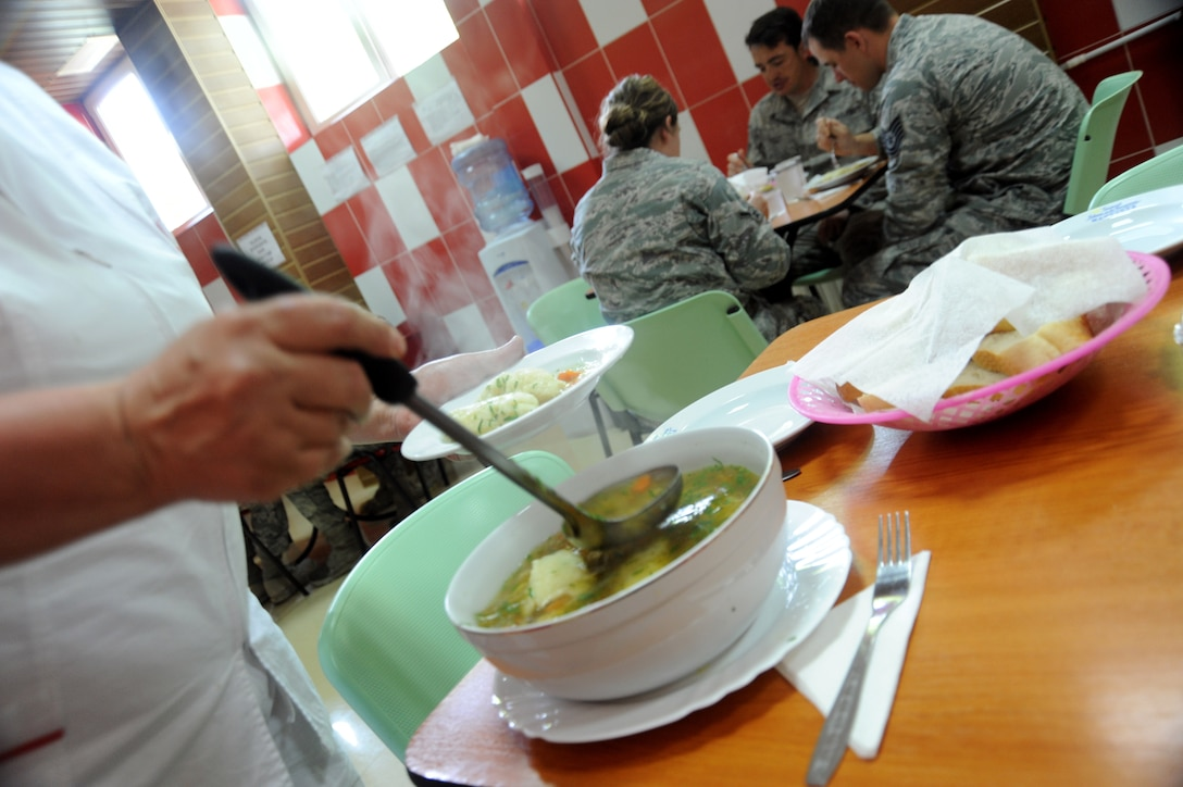 A food service worker at the Mangalia City Hospital, Romania serves a bowl of homemade soup to members of the 142nd Fighter Wing Civil Engineer Squadron (CES), Oregon Air National Guard. May 19, 2015. The 142nd CES is taking part in U.S. European Command's (EUCOM) Humanitarian Civic Assistance Program (HCA). The EUCOM HCA program is designed to improve the host nation's critical infrastructure and the underlying living conditions of the civilian populace. (U.S. Air National Guard photo by Staff Sgt. Brandon Boyd 142nd Fighter Wing Public Affairs/Released)