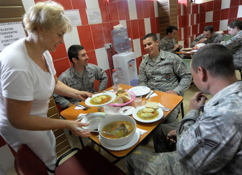 Oregon Air National Guard Airmen assigned to the 142nd Fighter Wing Civil Engineer Squadron take their lunch break with homemade soup provided by the staff at the local medical facility in the city of Mangalia, Romania, May 18, 2015, as part of the U.S. European Command's (EUCOM) Humanitarian Civic Assistance Program (HCA). The EUCOM HCA program is designed to improve the host nation's critical infrastructure and the underlying living conditions of the civilian populace. (U.S. Air National Guard photo by Tech Sgt. John Hughel, 142nd Fighter Wing Public Affairs/Released)