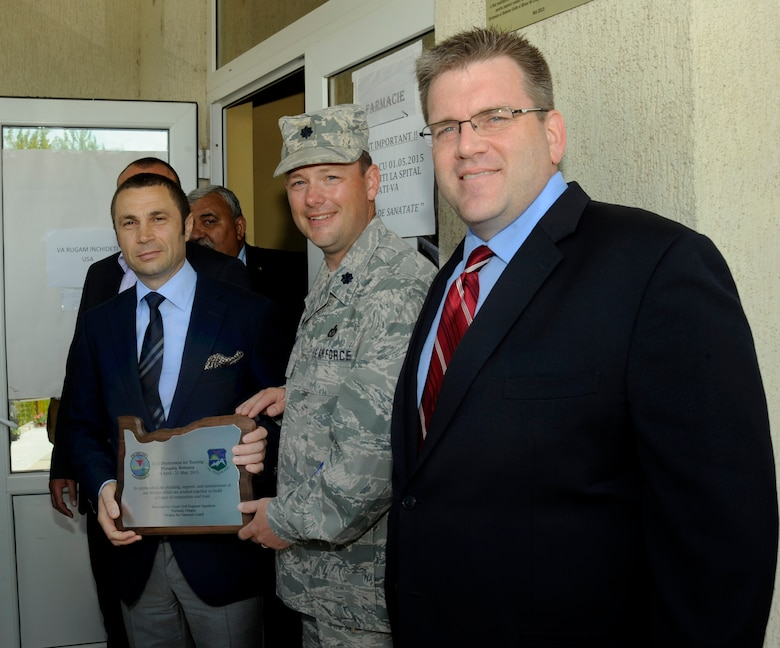 U.S. Charge d'Affairs a.i., Dean Thompson, right, along with and Mayor of Mangalia, Romania, Radu Cristian, left, pause for a photograph with Lt. Col. Jason Lay, 142nd Fighter Wing Civil Engineer Squadron, center, as he presents a plaque to the Mayor, after the ribbon cutting of the renovated Pavilion C of the Mangalia City Hospital, Romania, May 20, 2015, as part of the U.S. European Command's (EUCOM) Humanitarian Civic Assistance Program (HCA). The EUCOM HCA program is designed to improve the host nation's critical infrastructure and the underlying living conditions of the civilian populace. (U.S. Air National Guard photo by Tech. Sgt. John Hughel, 142nd Fighter Wing Public Affairs/Released)