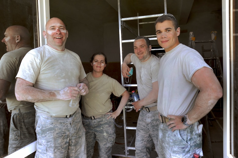 Oregon Air National Guardsmen (left to right) Chief Master Sgt. Brian Wade, Airman Hannah Phillips, Master Sgt. Robert Vickery and Staff Sgt. Jared Levitt, assigned to the 142nd Fighter Wing Civil Engineer Squadron, pause for a photograph while taking a break from sanding plaster inside a clinic treatment room at a medical being repaired in the city of Mangalia, Romania, May 13, 2015, as part of the U.S. European Command's (EUCOM) Humanitarian Civic Assistance Program (HCA). The EUCOM HCA program is designed to improve the host nation's critical infrastructure and the underlying living conditions of the civilian populace. (U.S. Air National Guard photo by Tech. Sgt. John Hughel, 142nd Fighter Wing Public Affairs/Released)