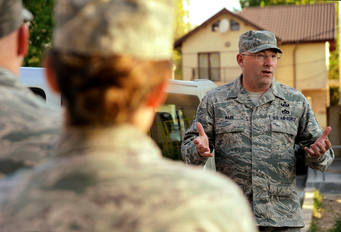 Oregon Air National Guard Chief Master Sgt. Brain Wade, assigned to the 142nd Fighter Wing Civil Engineer Squadron, leads a morning discussion to a group of Airmen beginning the work day in the city of Mangalia, Romania, May 12, 2015, as part of the U.S. European Command's (EUCOM) Humanitarian Civic Assistance Program (HCA). The EUCOM HCA program is designed to improve the host nation's critical infrastructure and the underlying living conditions of the civilian populace. (U.S. Air National Guard photo by Tech Sgt. John Hughel, 142nd Fighter Wing Public Affairs/Released)