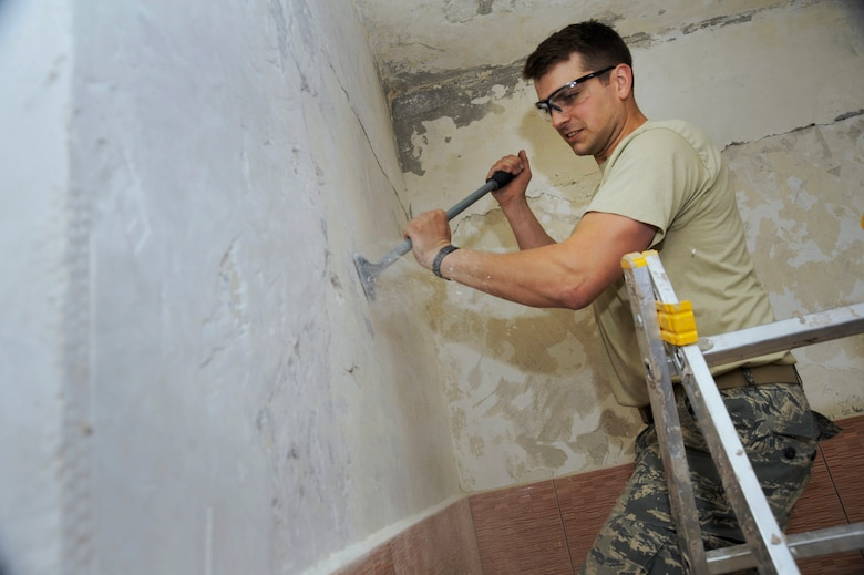 Oregon Air National Guard Senior Airman Zachariah Lewis, assigned to the 142nd Fighter Wing Civil Engineer Squadron, uses a scraper to remove paint from a medical treatment room inside a health clinic at the city of Mangalia, Romania, May 8, 2015, as part of the U.S. European Command's (EUCOM) Humanitarian Civic Assistance Program (HCA). The EUCOM HCA program is designed to improve the host nation's critical infrastructure and the underlying living conditions of the civilian populace. (U.S. Air National Guard photo by Tech. Sgt. John Hughel, 142nd Fighter Wing Public Affairs/Released)