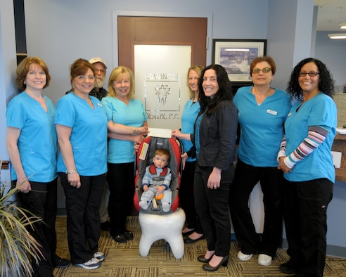 Ms. Mary Grace Scarpelli (second from left), Operation Whiter-Brighter Coordinator from Advanced Dental presents a check for $3,600 to Captain Gina Pizziconi Cupples (third from right), President of Friends of Family Support Association, Niagara Falls Air Reserve Station at the Advanced Dental office in Niagara Falls, N.Y. on May 20, 2015. Looking on are (left to right) Ms. Carla Siwinski, dental assistant, Dr. Stuart J. Weinstein, dentist/owner, Ms. Luann Pelletier dental assistant, Chance Cupples, (future patient?), Ms. Wendy Mariano, dental assistant, Ms. Susan Yuroshoski, supervising assistant, and Ms. Cindy Garner, dental assistant.  The program now in its ninth year at Advanced Dental of Niagara Falls, New York offers professional whitening at a greatly reduced cost to all patients.  100% of all proceeds from the program are donated to the Base Family Readiness Center. The money will be used for various programs to benefit local military members and their families. (U.S. Air Force photo by Peter Borys)